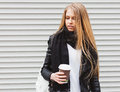 Portrait of a beautiful young blonde girl with long hair posing on a street with coffee and a backpack. Outdoor, warm color. Close Royalty Free Stock Photo