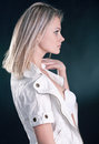 Portrait of a beautiful young blonde girl in white jacket and black skirt on dark background Stock Image