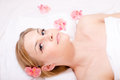 Portrait of beautiful young charming attractive blond woman relaxing lying during spa procedures surrounded with flowers looking Royalty Free Stock Image
