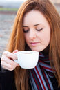 Portrait  of a beautiful young girl enjoying drinking coffee Royalty Free Stock Image