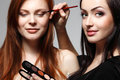 Portrait of beautiful young redheaded woman with esthetician mak women making makeup eye shadow Royalty Free Stock Photography