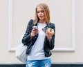 Portrait of a beautiful young sexy woman eating a donut, looks at her smart phone on the street European city. Outdoor. Royalty Free Stock Photo