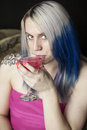 Portrait beautiful young woman blue hair pink dress holding pink martini Royalty Free Stock Images