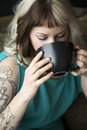 Portrait of a beautiful young woman with brown and blond hair looking right into the camera she is also holding a black coffee cup Royalty Free Stock Image