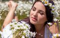 Portrait of a beautiful young woman in chamomile field. Happy girl collecting daisies. A girl resting in a field of chamomile. S Royalty Free Stock Photo