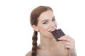 Portrait of a beautiful young woman eating a chocolate bar. Stock Image
