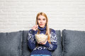 Portrait of beautiful young woman eating popcorn while watching movie in living room Royalty Free Stock Photo