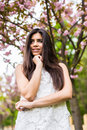 Portrait of beautiful young woman enjoying sunny day in park during cherry blossom season on a nice spring day Royalty Free Stock Photo