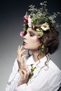 Portrait of beautiful young woman with flowers in hair isolated on dark background Stock Image