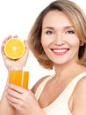 Portrait of a beautiful young woman with a glass of juice and orange isolated on white Stock Photos