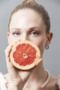 Portrait of Beautiful young woman with grapefruit in her hand Royalty Free Stock Photo