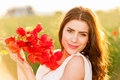Portrait of beautiful young woman holding poppies bouquet in the field Royalty Free Stock Photo
