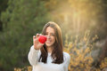Portrait of beautiful young woman holding red heart against forest Royalty Free Stock Photography