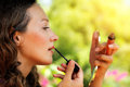 Portrait of beautiful young woman with lip gloss and mirror aga against green summer park Royalty Free Stock Photography
