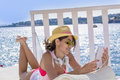 Portrait of beautiful young woman listening music on a sea background with straw hat with tablet summer vacation Royalty Free Stock Images