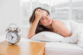 Portrait of a beautiful young woman lying in bed with alarm clock on bedside table Stock Image