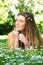 Portrait of a beautiful young woman lying on green grass outdoors close up Stock Photo