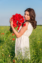 Portrait of beautiful young woman with poppies in the field with a poppies bouquet. Royalty Free Stock Photo