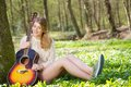 Portrait of a beautiful young woman relaxing with guitar outdoors Royalty Free Stock Photo