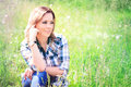 Portrait of a beautiful young woman sitting in the grass Royalty Free Stock Photo