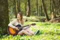 Portrait of a beautiful young woman smiling and playing guitar outdoors in the forest Royalty Free Stock Images