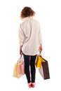 Portrait of a beautiful young woman walking away with shopping posing bags isolated on white background Royalty Free Stock Image