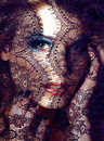 Portrait of beauty blond young woman through black lace close up