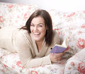 Portrait of beauty smiling woman with book reading on sofa at home Stock Images