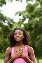 Portrait of black girl in love daydreaming and smiling ecology environment young african american touching her heart park with eye Stock Photos