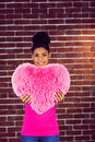 Portrait black hair model holding a pink heart shaped pillow Royalty Free Stock Photo