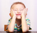 Portrait of blond boy child kid making funny face at the table cute silly interior emotions and fun Stock Photo