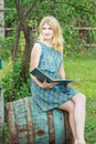 Portrait of blonde girl in feminine blue silk dress with opened book summer Royalty Free Stock Photography