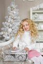 Portrait of blonde little girl sits on a sofa and touches a gift box in Christmas Royalty Free Stock Photo
