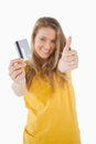 Portrait of a blonde student tending a credit card with the thum Royalty Free Stock Images