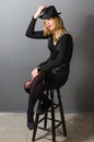 Portrait of blonde woman with a hat on bar stool sitting Royalty Free Stock Photos