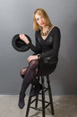 Portrait of blonde woman with a hat on bar stool sitting Stock Photography