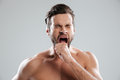 Portrait of a bored beraded man with naked shoulders yawning Royalty Free Stock Photo