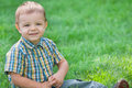 Portrait of a boy against the green grass Royalty Free Stock Photography