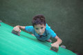 Portrait of boy climbing green wall Royalty Free Stock Photo