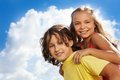 Portrait of boy and girl close two school age children carry on her back both happy smile on sunny day with clouds sky on Stock Photo
