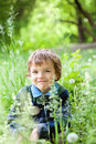 Portrait of boy sitting on grass in park Royalty Free Stock Image