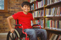 Portrait of boy sitting in wheelchair at library Royalty Free Stock Photo