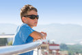 Portrait of a boy stands on the balcony hotel and looks into distance background mountains Royalty Free Stock Images