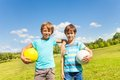 Portrait of boys with balls two brothers stand holding standing in the park on sunny summer day Royalty Free Stock Photography