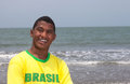 Portrait of a brazilian guy at beach football fan from brazil standing the with the ocean in the background and laughs camera Royalty Free Stock Photography