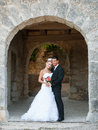 Portrait of bride and groom under stone arch in a park outdoor married couple Stock Photo