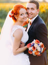 Portrait of bright happy redhair bride and handsome groom posing for camera in the sunny sunflower field Royalty Free Stock Photo