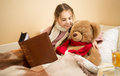 Portrait of brunette girl telling story to teddy bear at bed Royalty Free Stock Photo