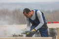 Portrait of builder working with circular saw outdoors, sawdust flying around Royalty Free Stock Photo