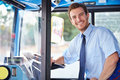 Portrait of bus driver behind wheel looking to camera smiling Royalty Free Stock Photography